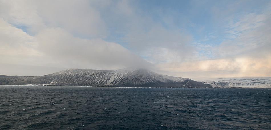 Saunders Island voraus, der 990 Meter über Meer liegende, noch aktive Vulkan Mount Michael liegt am frühen Morgen in den Wolken.